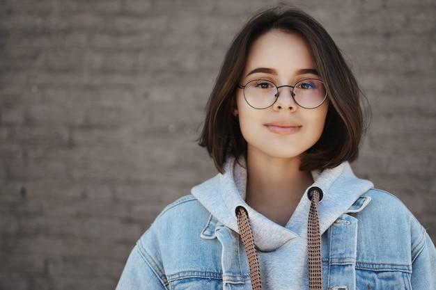 Retrato do close-up despreocupado otimista jovem aluna de cabelos curtos de óculos, ansioso por oportunidades de vida, sorrindo a câmera de olhar sonhadora, em pé perto da parede de tijolos ao ar livre.
