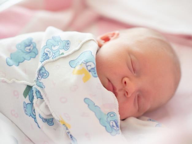 Retrato do close-up do bebê recém-nascido dormindo na camiseta