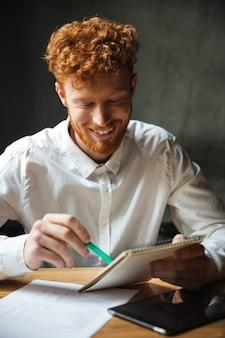 Retrato do close-up do belo estudante sorridente, estudando em casa