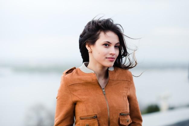 Retrato do close-up do casaco de couro vestindo da mulher atrativa bonita feliz nova que sorri e que está sobre a luz fora do fundo. o vento sopra o cabelo dela.