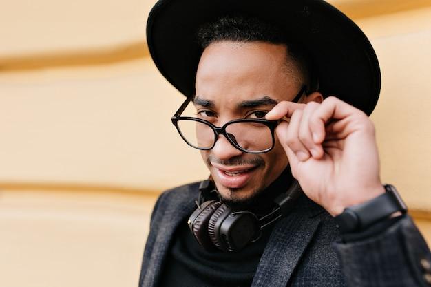 Retrato do close-up do homem africano positivo, brincando, tocando seus óculos. tiro ao ar livre do elegante modelo masculino preto em trajes da moda, isolado na rua da cidade.