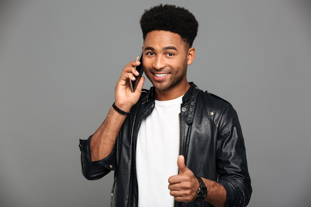 Retrato do close-up do homem afro-americano elegante sorridente, falando no celular enquanto mostra o polegar para cima gesto, olhando