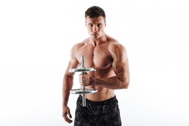 Retrato do close-up do homem atlético suado sério levantando halteres