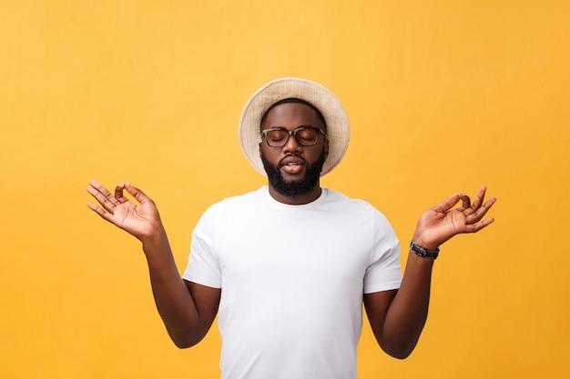 Retrato do close up do homem considerável, novo feliz no modo da ioga da meditação, isolado no fundo amarelo. conceito de técnicas de alívio de estresse.