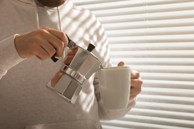 Retrato do close-up do homem jovem hippie elegante servindo café no escritório num dia de verão. manhã revigorante e humor positivo