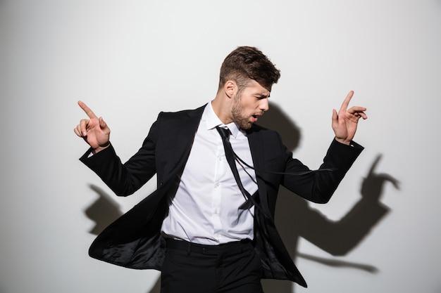 Retrato do close-up do jovem empresário, apontando com dois dedos para cima, olhando de lado