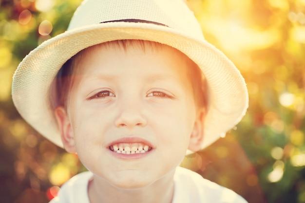 Retrato do close-up do menino de sorriso em um chapéu no dia de verão ensolarado.