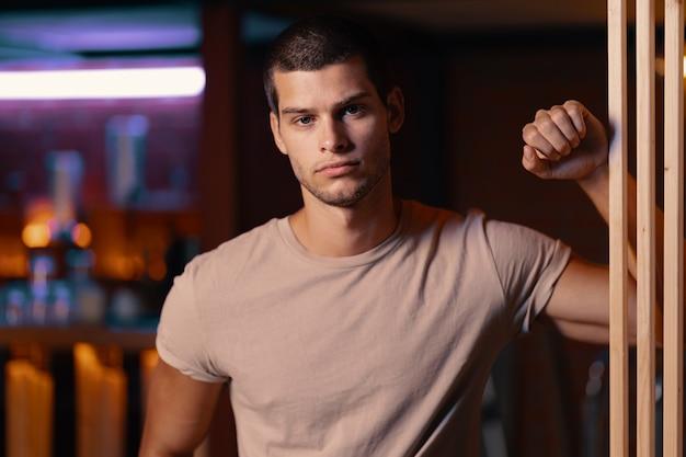 Retrato do close-up do modelo masculino atraente. jovem bonito em um bar