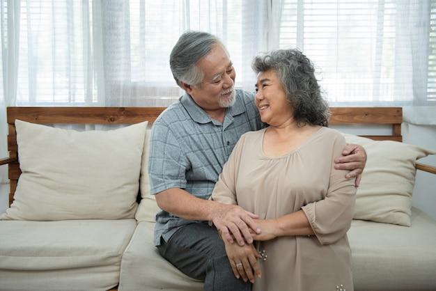 Retrato do close-up dos esposos calmos calmos alegres alegres delicados doces bonitos atrativos asiáticos superiores mais velhos que abraçam guardar de mãos dadas na sala interior branca clara, retrato de pares da aposentadoria.