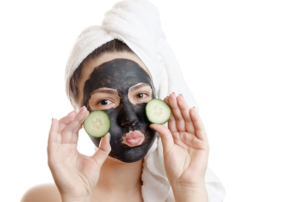 Retrato do close-up, mulher bonita com máscara facial preta e fatias de pepino nas mãos, sobre fundo branco, garota com uma toalha branca na cabeça, beijo no ar