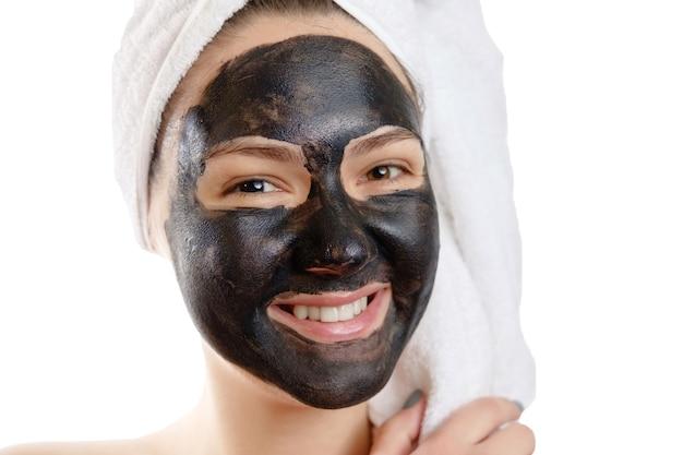 Retrato do close-up, mulher bonita com máscara facial preta em fundo branco, garota com uma toalha branca na cabeça, sorriso satisfeito e feliz