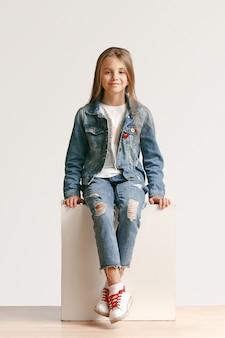 Retrato do comprimento total da menina adolescente bonitinha com roupas jeans elegantes, olhando para a câmera e sorrindo contra a parede branca do estúdio. conceito de moda infantil