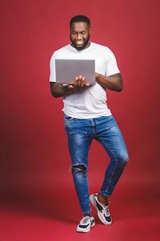 Retrato do comprimento total do homem afro-americano feliz animado com tela de computador e comemorar a vitória isolada sobre fundo vermelho. afirmativo.