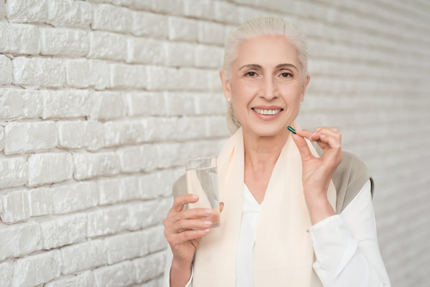 Retrato do comprimido bebendo da mulher madura com água.