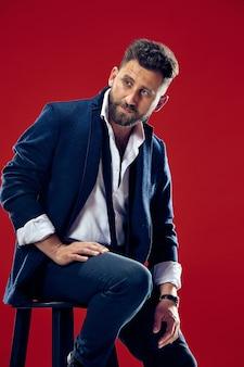 Retrato do conceito de beleza masculina de um jovem elegante com um corte de cabelo estiloso, vestindo um terno da moda posando sobre a parede vermelha