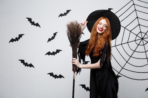 Retrato do conceito de bruxa de halloween da bela jovem bruxa com vassoura sobre parede cinza com parede de morcego e teia de aranha