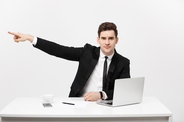 Retrato do conceito de negócio do empresário bonito vestido de terno, sentado no escritório, apontando o dedo ...