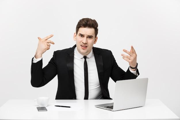 Retrato do conceito de negócio do empresário com raiva gritando, sentado no escritório, isolado sobre o fundo branco.