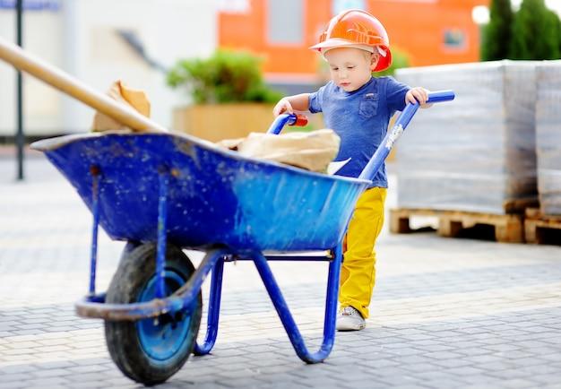 Retrato do construtor bonito da criança nos capacete de segurança com o carrinho de mão que trabalha fora.
