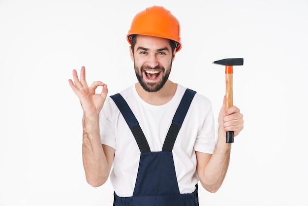 Retrato do construtor de jovem alegre feliz posar de capacete isolado sobre a parede branca, segurando o martelo, mostrando o gesto certo.