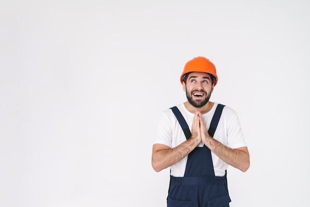 Retrato do construtor de jovem sonhando positivo no capacete posando isolado sobre uma parede branca.