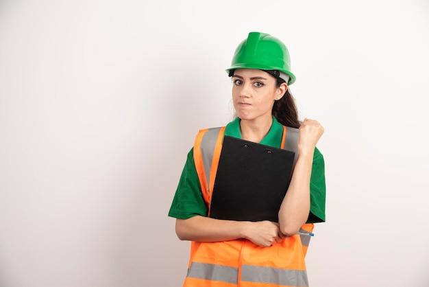 Retrato do construtor de mulher bem sucedida usando capacete e colete laranja de segurança. foto de alta qualidade