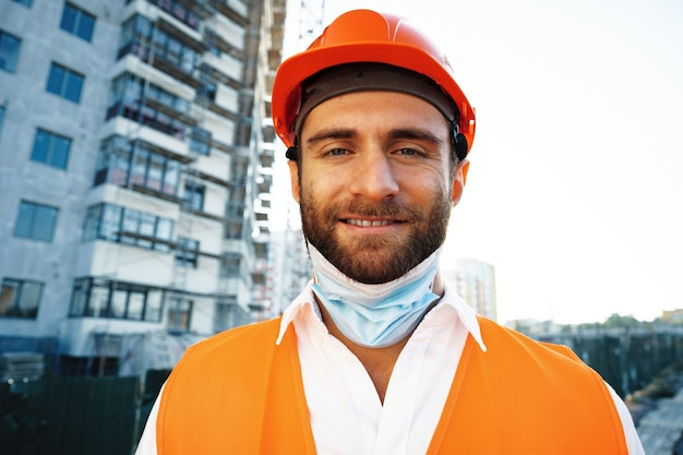 Retrato do construtor em traje de trabalho e capacete de segurança, usando máscara médica, close-up