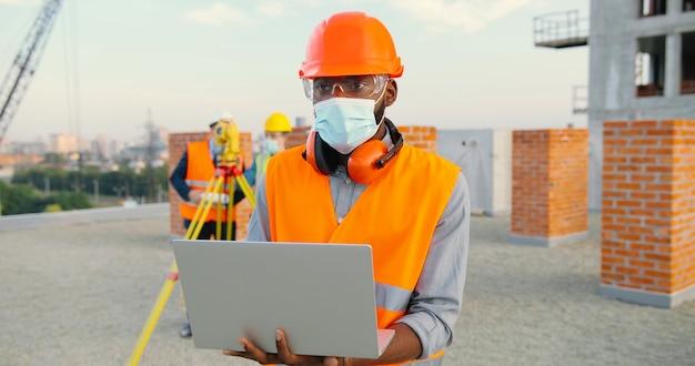 Retrato do construtor masculino afro-americano ou construtor na máscara médica e capacete de segurança usando o computador portátil em pé no canteiro de obras.