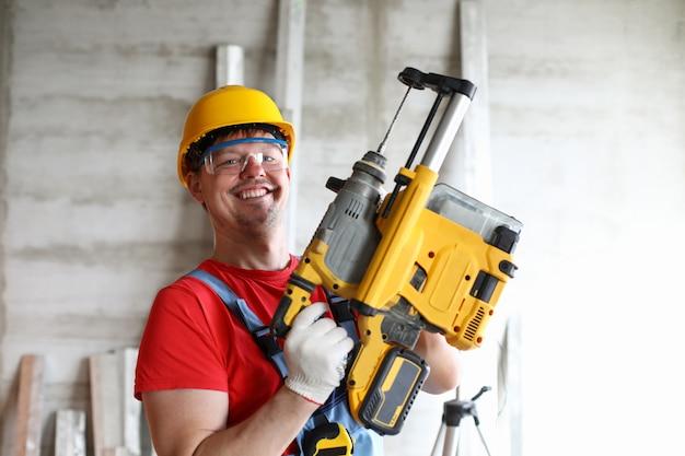Retrato do construtor sorridente em macacão, óculos de proteção e capacete.