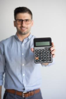 Retrato do contador feliz nos vidros que mostram a calculadora.