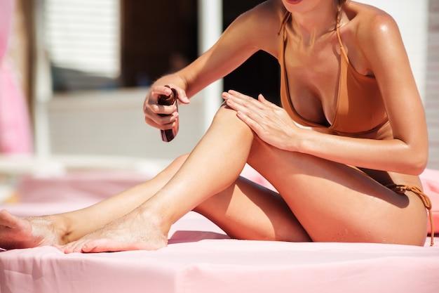 Retrato do corpo de uma mulher bonita em biquíni, sentado na cama da praia.