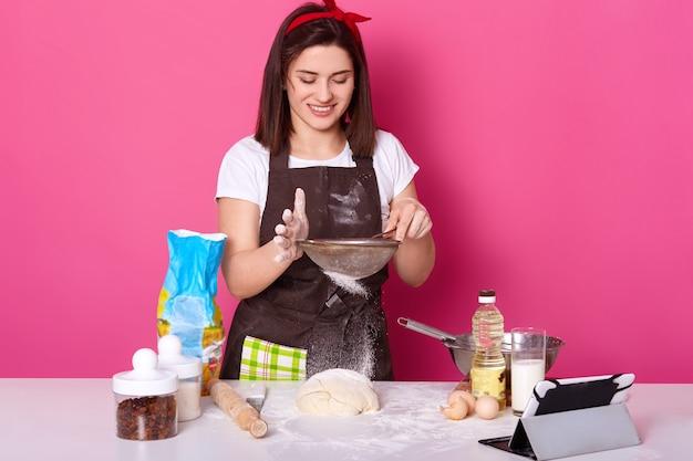 Retrato do cozinheiro talentoso hábil que põe a farinha através da peneira na torta meio pronta com passas. poses de modelo jovem bonito morena isoladas em rosa brilhante. cozimento e culinária conceito.