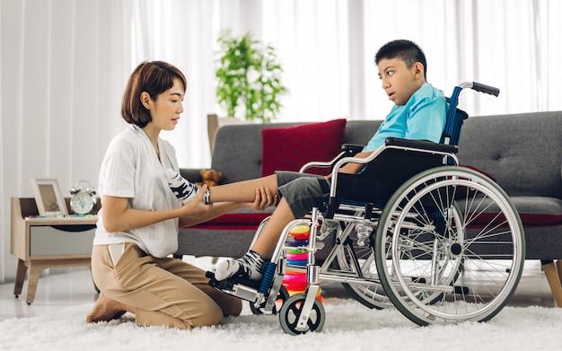 Retrato do cuidador asiático fisioterapeuta ajudando e brincando com o problema de saúde da criança com deficiência especial, fazendo exercícios, sentado na cadeira de rodas na clínica de reabilitação. conceito de cuidados com deficiência