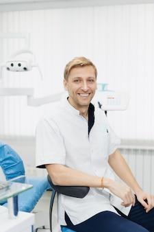 Retrato do dentista de homem caucasiano sorridente, posando no consultório odontológico moderno.
