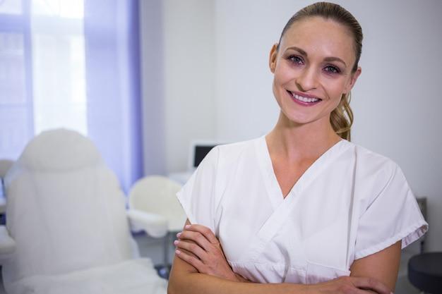 Retrato do dentista em pé com os braços cruzados