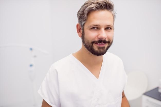 Retrato do dentista em pé na clínica