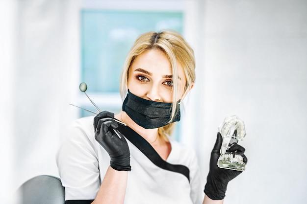 Retrato do dentista fêmea consideravelmente novo em uma clínica dental.
