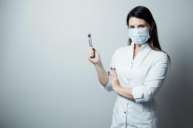Retrato do dentista fêmea. ela que está em seu escritório do dentista. dentista feminina vestindo uma túnica branca
