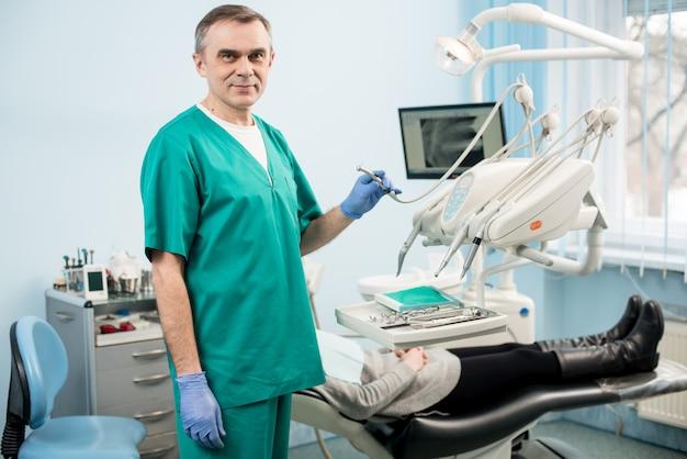 Retrato do dentista masculino considerável com as ferramentas dentais na clínica dental. no paciente de segundo plano e monitore com raio-x os dentes do paciente