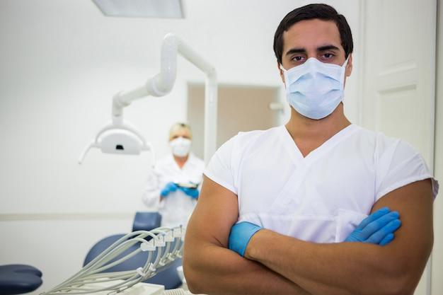 Retrato do dentista masculino em pé com os braços cruzados