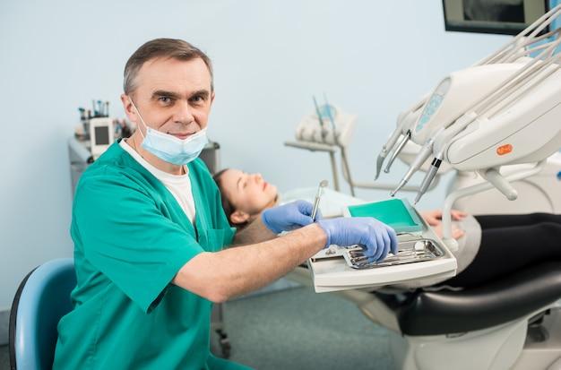 Retrato do dentista masculino sênior com equipamento dental no consultório odontológico.