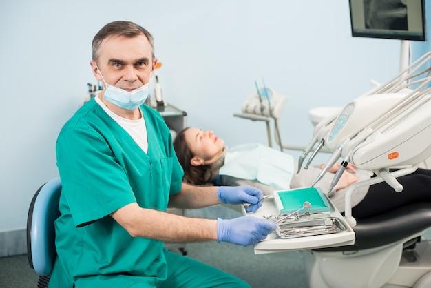 Retrato do dentista masculino sênior com instrumentos dentários no consultório odontológico