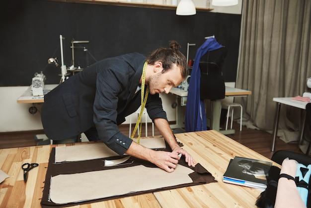 Retrato do desenhador de moda latino-americano bonito novo sério no terno preto que corta as partes do revestimento para a coleção do inverno com expressão concentrada da cara.