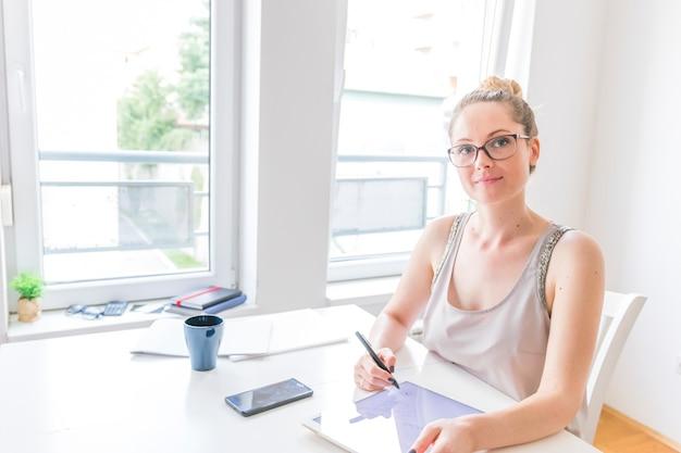 Retrato do desenhista fêmea gráfico esperto que usa a tabuleta digital gráfica no local de trabalho