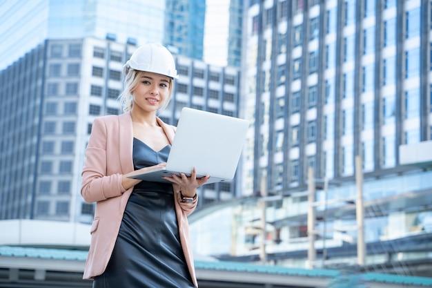 Retrato do desenvolvedor de engenheiro de mulher bonita ásia negócios segurando laptop trabalhando confiável ao ar livre no canteiro de obras.
