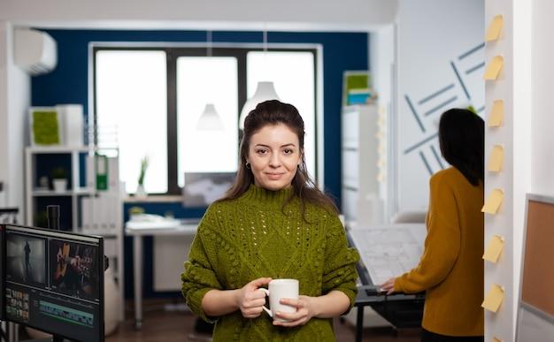 Retrato do designer criativo sorrindo para a câmera segurando uma xícara de café em pé no escritório da agência start up