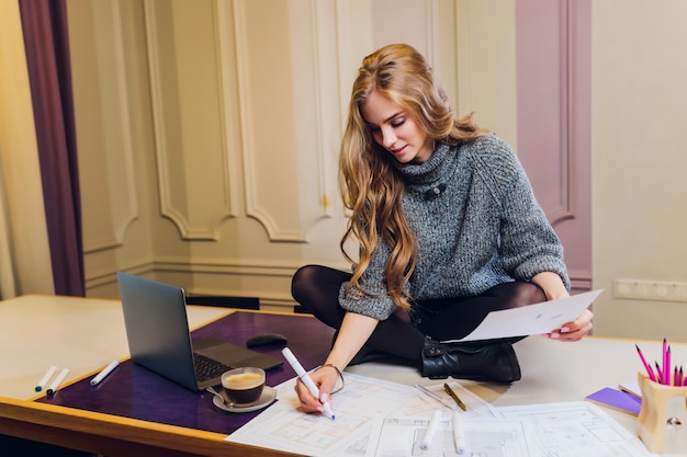 Retrato do designer de interiores fêmea de sorriso que senta-se na mesa de escritório.