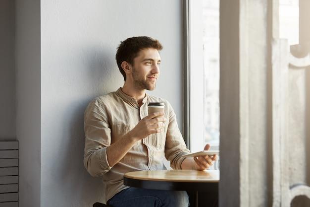 Retrato do designer freelancer masculino jovem perspectiva sentado na cafeteria, olhando de lado sendo satisfeito com seu novo projeto.
