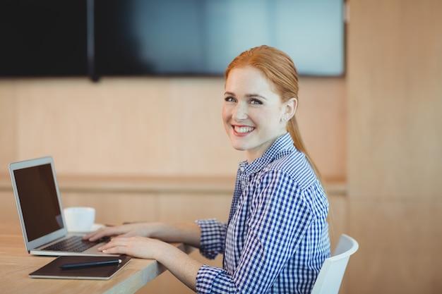 Retrato do designer gráfico feminino usando laptop