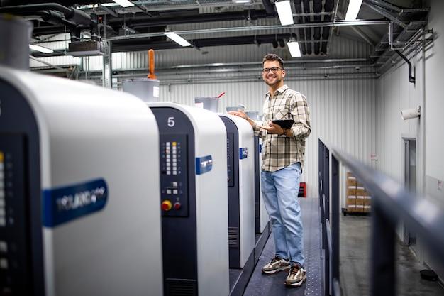 Retrato do designer gráfico ou engenheiro verificando a produção na máquina de impressão na fábrica de impressão